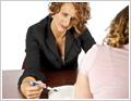 תמונה של תלמידה יושבת ליד שולחן ומולה יושבת מורה, מאבחנת ומצביעה בעט על שורה בספר.