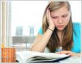 תלמידה יושבת עם ספר פתוח. ראשה נשען על כף היד. פניה מביעות ייאוש.